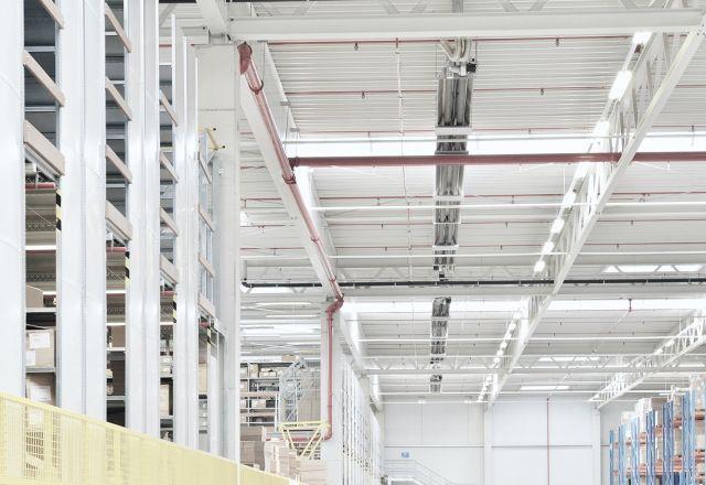 Długie promienniki rurowe firmy Schwank pod sufitem budynku logistycznego.